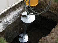 Installing a helical pier system in the earth around a foundation in Warren