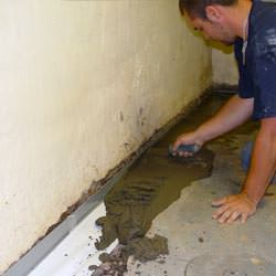 A basement waterproofer installing a perimeter drain system in Pontiac